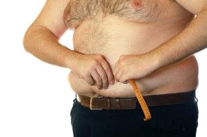 fat man measuring his belly against the white background
